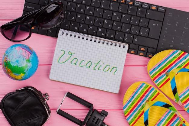 ピンクのテーブルトップに女性の旅行者アクセサリーメガネ財布とフリップフロップとノートブックでの休暇...