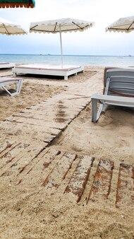 Отдых на песчаном пляжном шезлонге с зонтиками на тихом спокойном голубом берегу океана, побережье летом. пейзаж морского песчаного берега. расслабьтесь и расслабьтесь.