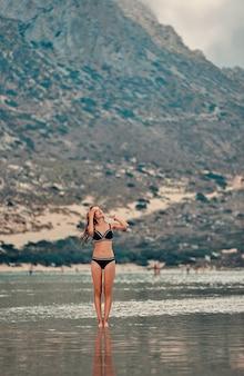 해변에서 휴가. 아름다운 자연 바위 풀의 전망을 즐기는 매력적인 젊은 여자. 여행, 레저, 관광의 개념.