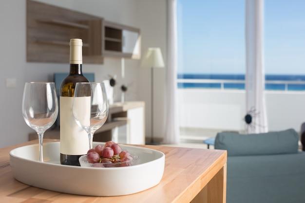 Комната отдыха с видом на море и столиком с бутылкой вина и бокалами.