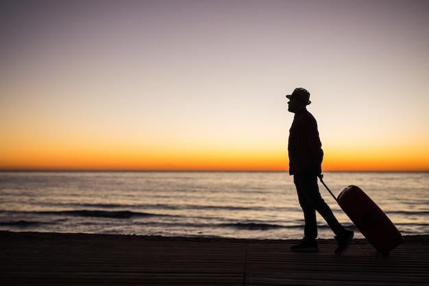 休暇、夏、旅行のコンセプト-海の近くの日没時のスーツケースと若い男のシルエット。