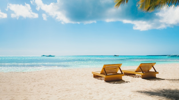 Vacation summer holidays background - sunny tropical caribbean blue lagoon paradise beach with white sand palms, and loungers