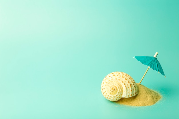 Отдых, лето, релаксация и море концепции фон. минимальная творческая композиция с песком и зонтиком на цветном чистом фоне.