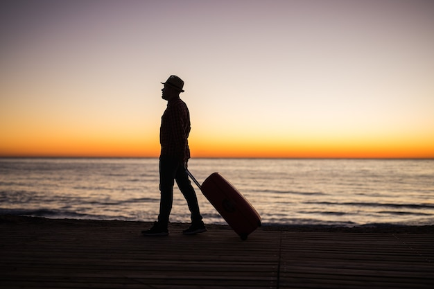 Vacation, summer and travel concept - young man silhouette with suitcase at sunset near the sea.
