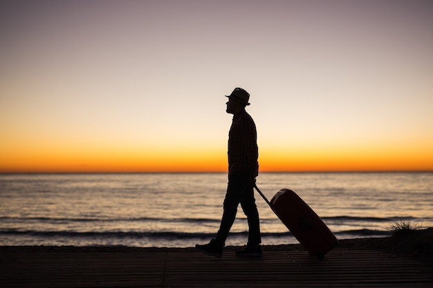Vacation summer and travel concept  young man silhouette with suitcase at sunset near the sea