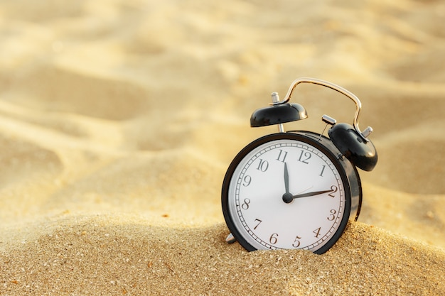 Vacation time, alarm clock on the sand