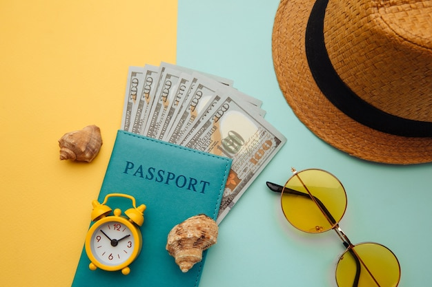 休暇旅行冒険旅行のコンセプト。イエローブルーの表面に帽子、パスポート、シェルを備えた最小限のシンプルなフラットレイ。観光の必需品