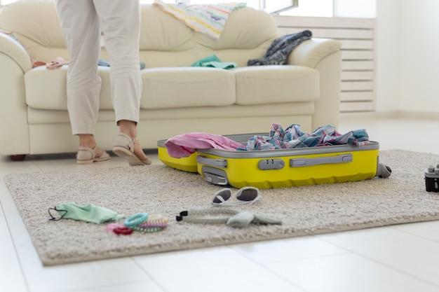 Концепция отпуска, путешествий и праздников - открытие чемодана, лежащего на полу, вид сверху.