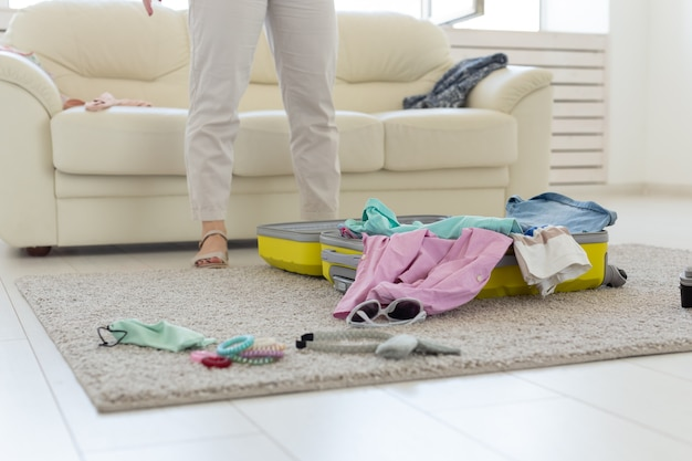 休暇、旅行、休日のコンセプト-床に横たわってスーツケースを開く