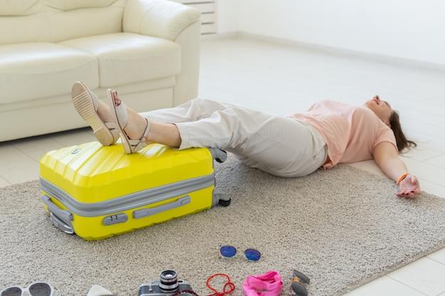 Концепция отпуска, путешествий и праздников - женщина пытается закрыть чемодан с множеством вещей