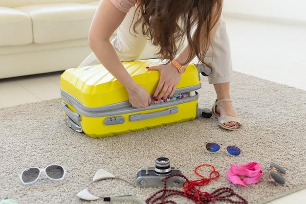 休暇、旅行、休日のコンセプト-たくさんのものでスーツケースを閉じようとしている女性。