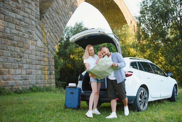 Vacation, travel - семья готова к путешествию на летние каникулы. чемоданы и автомобильный маршрут. люди с картой в руках планируют поездку. концепция путешествия. путешественник.