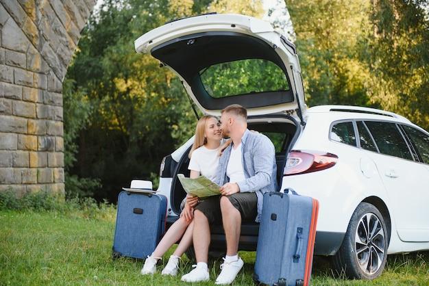 Vacation, travel - семья готова к путешествию на летние каникулы. чемоданы и автомобильный маршрут. люди с картой в руках планируют поездку. концепция путешествия. путешественница.