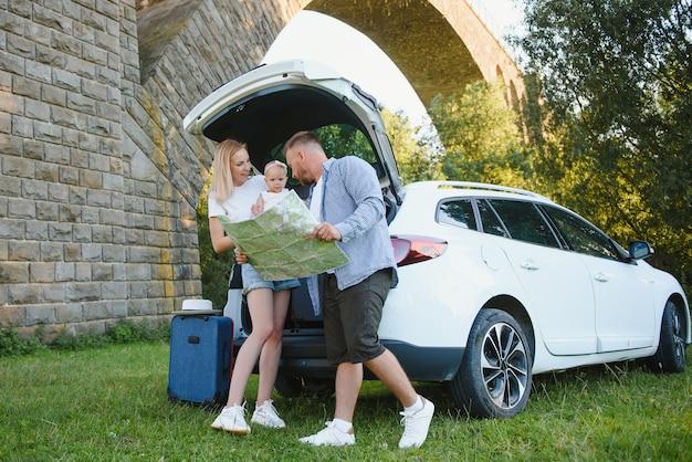 휴가, 여행 - 여름 휴가를 위한 여행 준비가 된 가족. 가방 및 자동차 경로입니다. 손에 지도를 들고 도로 여행을 계획하는 사람들. 여행 개념입니다. 여행자.