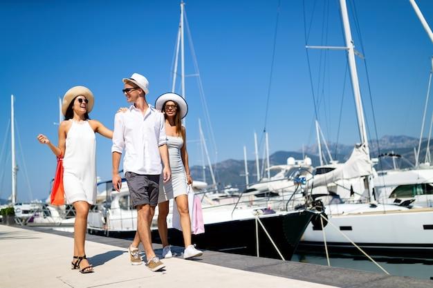 휴가, 여행, 바다, 우정, 그리고 사람들의 개념. 함께 즐겁게 웃고 있는 친구들
