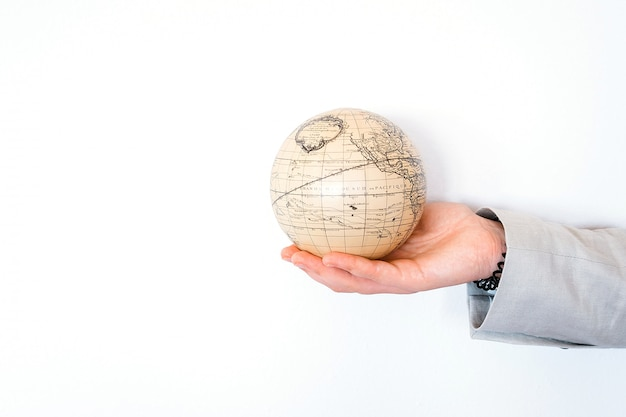 Vacation travel summer weekend adventure trip concept. vintage antique globe in hand isolated on white background. copy space. mock up for turism agency. education and discovery idea