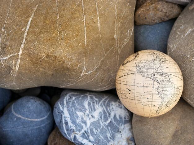 Vacation travel summer weekend sea adventure trip concept. vintage antique globe in hand on rocks background.
