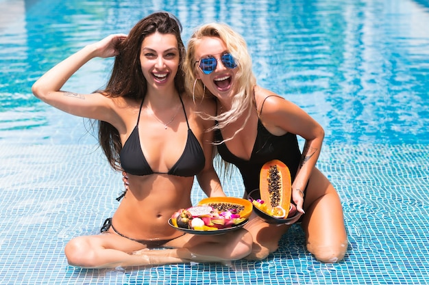 Vacation tropical portrait to two slow girls, with amazing long blonde and brunette hairs, sitting back to camera, wearing lack bikinis posing at pool holding plates with exotic fruits,