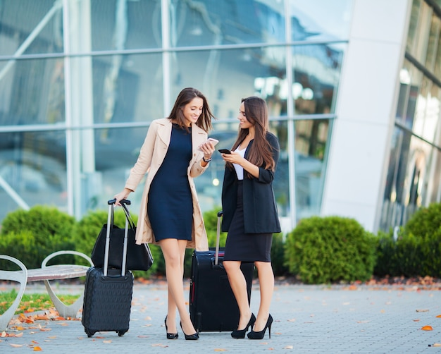 Vacation, two happy girls traveling abroad together, carrying suitcase luggage in airport