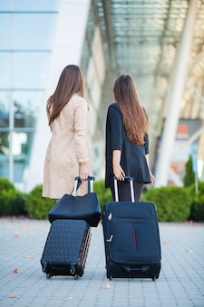 Vacation. two stylish female travelers walking with their luggage in airport
