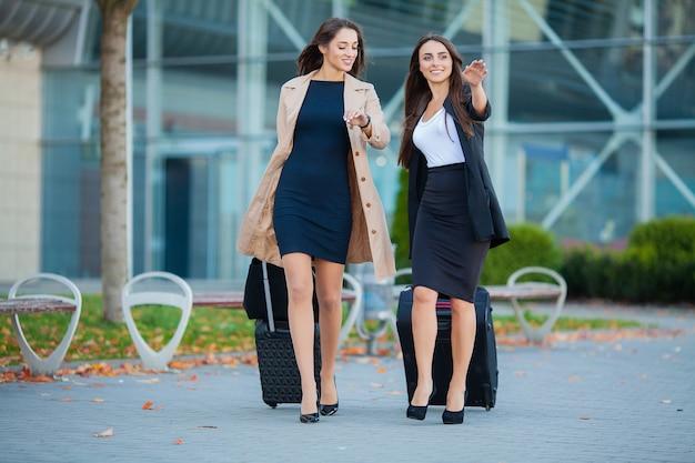休暇。空港で荷物を持って歩く2人のスタイリッシュな女性旅行者