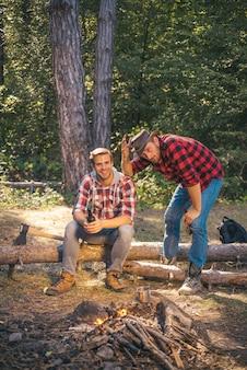 休暇の週末のピクニックキャンプとハイキング会社の大人の友人がキャンプファイヤーキャンプの冒険の近くでリラックスしています...