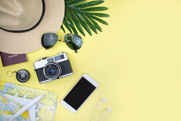 Vacation with a hat, map, smartphone, film camera and sunglasses on a yellow background. top view.
