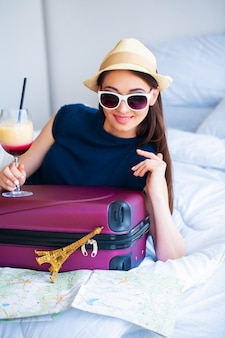 Vacation. woman who is preparing for rest. young beautiful girl sits on the bed and holds in the hands cocktail. portrait of a smiling woman. happy girl goes on vacation
