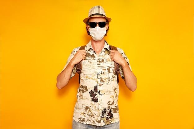 노란색 배경에 배낭을 메고 선글라스 의료 마스크를 쓴 휴가 중인 남자 관광 여행자