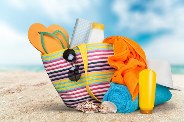 バケーションコンセプト、サマービーチのビーチアイテムが入ったカラフルなバッグ