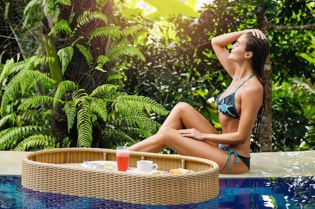 리조트에서의 휴가. 수영장에 떠있는 아침 식사와 함께 젊은 행복 한 여자.