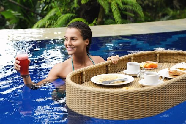 Отдых на курорте. молодая счастливая женщина с плавающим завтраком в бассейне.