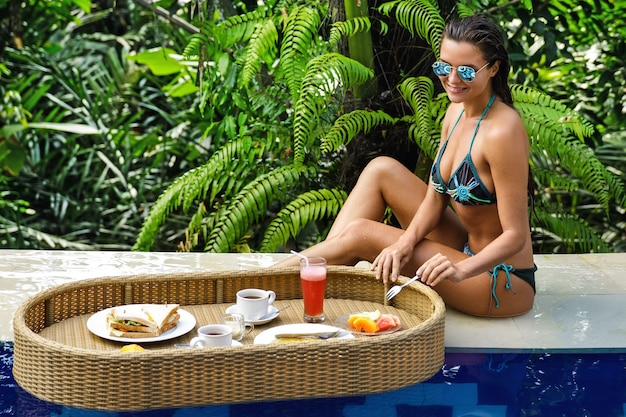 Vacations in the resort. young happy woman with a floating breakfast in the pool.