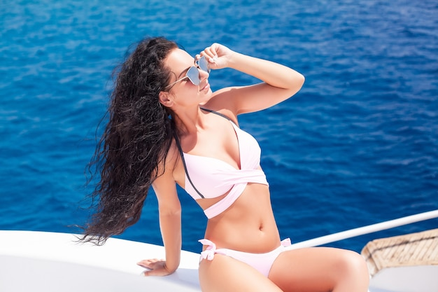 Vacations. sexy long hair girl in swimwear on yacht in montenegro.