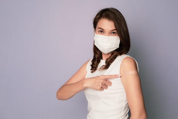 Covid-19ワクチン注射を受けた後、腕に絆創膏を見せているワクチン接種を受けたアジア人女性と、医療衛生フェイスマスクを着用して座っている間笑顔。コロナウイルスワクチン接種キャンペーンのコンセプト。