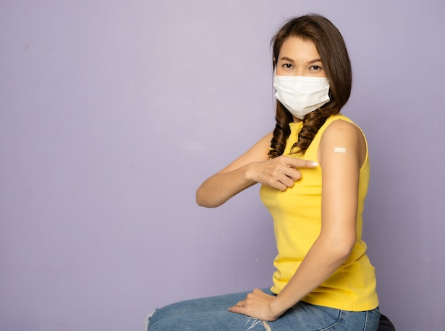 保護医療衛生フェイスマスクを着用して座っているときにcovid-19ワクチン注射を受けた後、腕に絆創膏を示すワクチン接種を受けたアジア人女性。コロナウイルスワクチン接種キャンペーンのコンセプト。
