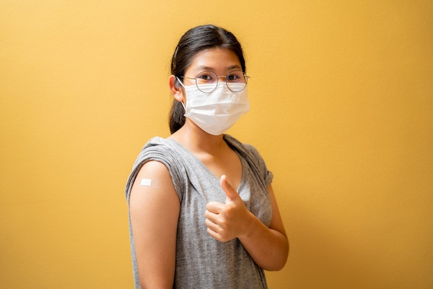 Vaccinated asian teen girl in face mask showing plaster bandage on her arm after getting covid-19 vaccine injection on yellow studio background. coronavirus population immunization campaign