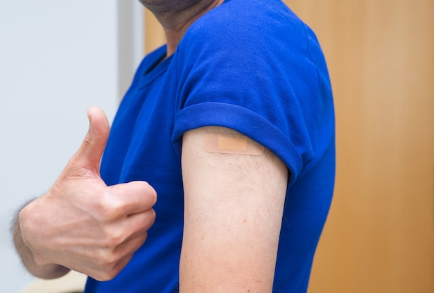 Vaccinated man making the finger up gesture. Premium Photo