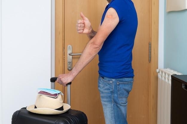 Вакцинированный мужчина с пластырем на руке уезжает из дома в отпуск. дорожный чемодан со шляпой и паспортом. скопируйте пространство.