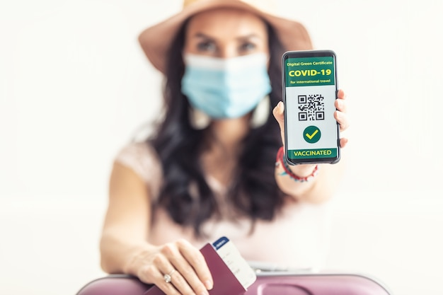 Vaccinated woman shows her digital green certificate for covid-19 in her mobile phone with passport and flight ticket, face mask on, ready to go.
