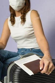 여행 가방에 covid-19 코로나바이러스 예방 접종 기록 카드와 여권을 들고 위생 보호 의료 마스크를 쓴 예방 접종을 받은 여성. 바이러스 발생 후 삶에 대한 개념. 뉴 노멀 아이디어.