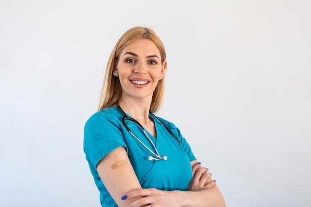 予防接種を受けた若い医師、医療従事者、予防接種を承認する看護師の女性、白い背景