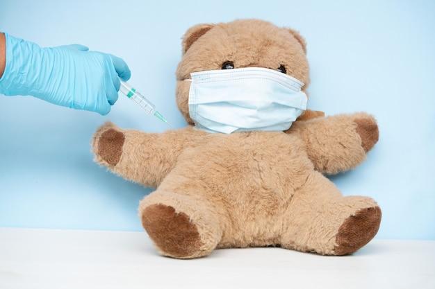 保護医療用フェイスマスク、covid 19、はしかの予防接種のコンセプトを身に着けているぬいぐるみのクマの予防接種