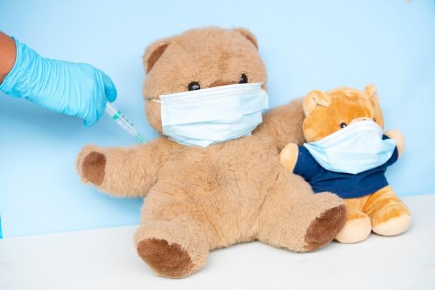 保護医療用フェイスマスク、covid 19、はしかの予防接種のコンセプトを身に着けている2つのぬいぐるみのクマの予防接種