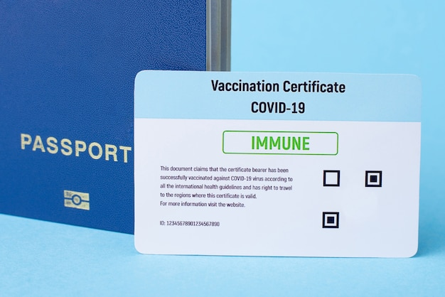 Vaccination certificate and passport on blue background