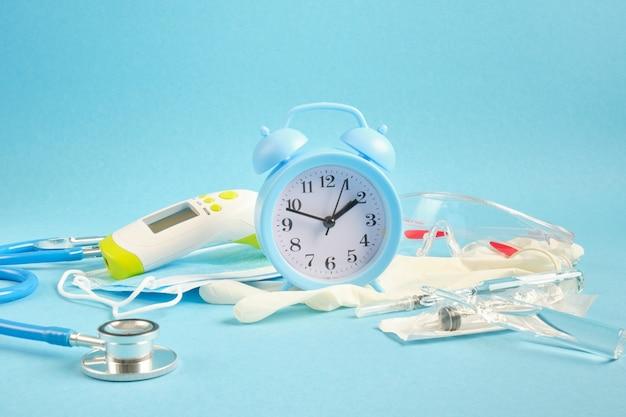 Концепция вакцинации будильник и медицинское оборудование на синем фоне поместите копию термометра, стетоскоп, маску для лица и шприцы для вакцинации