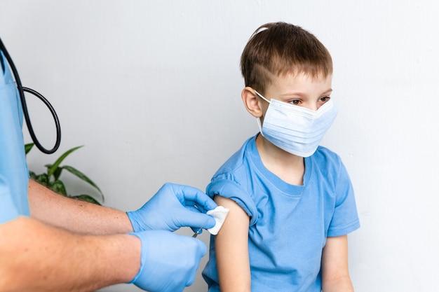 予防接種の概念。クリニック、クローズアップでかわいい男の子に予防接種をする男性医師。コロナウイルスcovid-19に対するワクチン接種セッションと免疫力の向上