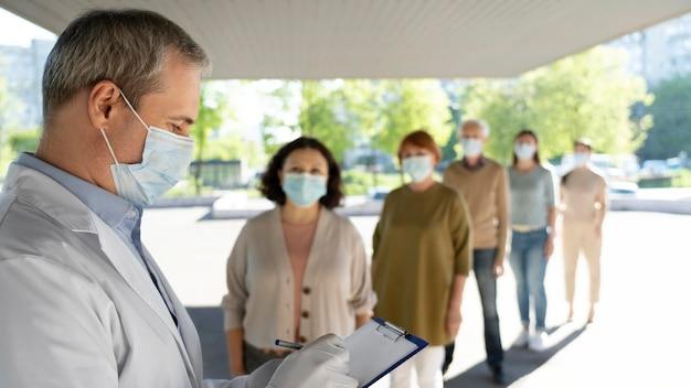 Врач вакцинации в центре заполняет информацию о пациентах в блокноте