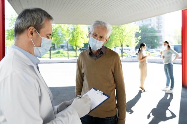 Medico di vaccinazione al centro che riempie le informazioni sui pazienti sul blocco note