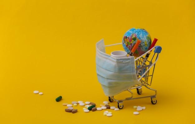백신 접종. 세계적 대유행 치료. 노란색 배경에 의료용 마스크, 글로브, 알약, 주사기가 있는 쇼핑 트롤리